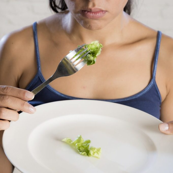 young woman holding dish with ridiculous lettuce as her food symbol of crazy diet nutrition disorder