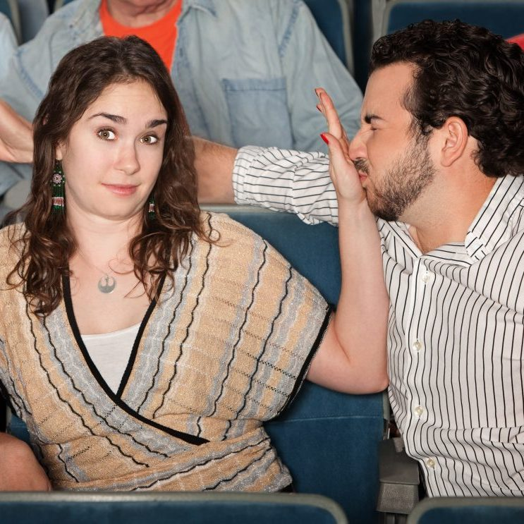Irritated girlfriend stops bad breath boyfriend in theater